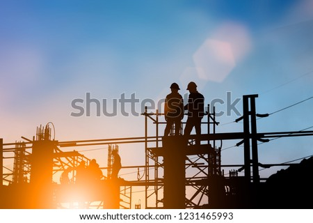 Silhouette of engineer and construction team working at site over blurred background for industry background with Light fair. #1231465993