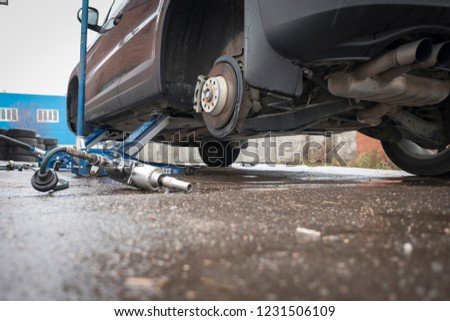 The car is lifted on jacks without wheels. Repair, tire installation. #1231506109