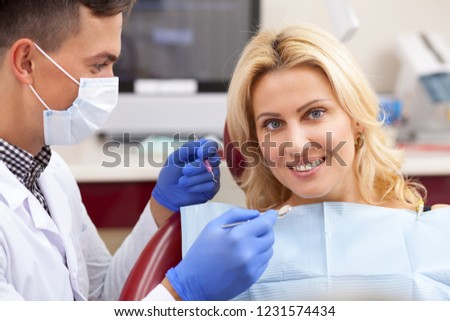 Beautiful happy mature woman with healthy perfect teeth smiling, sitting at the dental chair. Attractive female patient smiling joyfully during teeth examination by professional dentist. Dentistry #1231574434