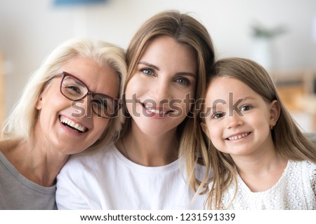 Headshot portrait of three 3 generations family, smiling grandmother, grown young daughter and child girl looking at camera, happy kid granddaughter, mother and old aged grandma posing together #1231591339