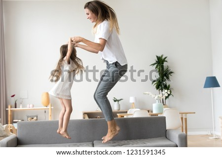 Happy mommy and kid daughter holding hands jumping on sofa together, baby sitter or mother playing having fun with cute kid girl at home, young mum and child enjoy spending time laughing together #1231591345