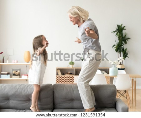 Cute little girl having fun playing with smiling grandmother jumping on couch together, happy granny and active kid grandchild dancing on sofa, grandma and granddaughter laughing playing at home #1231591354