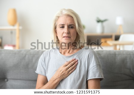 Upset stressed mature middle aged woman feeling pain ache touching chest having heart attack, sad worried senior older lady suffers from heartache at home, infarction or female heart disease concept #1231591375