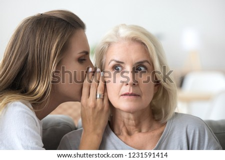 Shocked older woman listening to young female whispering in ear, friend gossiper telling secret rumors or unbelievable news to surprised senior lady, old mother and adult daughter gossiping concept #1231591414