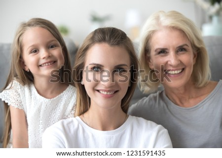 Smiling young adult woman looking at camera with old mother and little kid daughter, millennial mom posing with child girl and grandmother, happy three generation family together, headshot portrait #1231591435