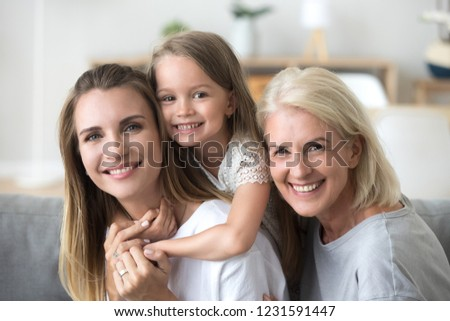 Happy three women generation, smiling young mother piggybacking little kid daughter looking at camera with old grandma, senior grandmother millennial mom and child together, family headshot portrait #1231591447