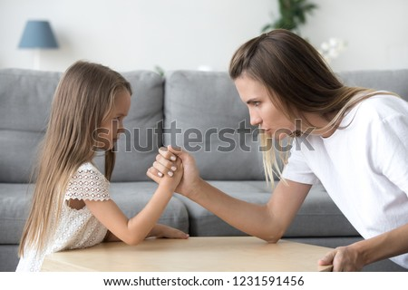 Mom and kid daughter arm wrestling having fight confrontation or family conflict, mother in law and stubborn child girl holding hands competing with serious focused faces expressing disagreement #1231591456