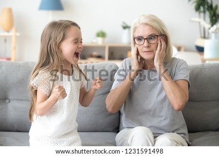 Shocked grandma closing ears not to hear noisy stubborn fussy little granddaughter screaming demanding attention, preschool spoiled kid girl yelling at grandmother, child tantrum manipulation concept #1231591498