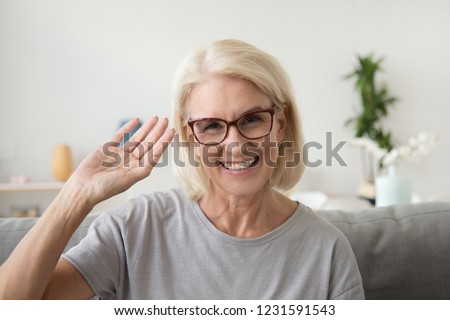 Smiling middle aged woman waving hand looking at camera, older mature lady in glasses making video blog or call at home, happy friendly senior vlogger sitting on sofa dating online, headshot portrait #1231591543