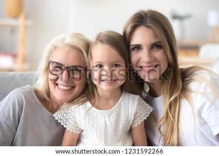 Happy family of grandmother, daughter and child girl looking at camera, smiling kid granddaughter posing with young mother and senior old mature grandma, three generations of women headshot portrait #1231592266
