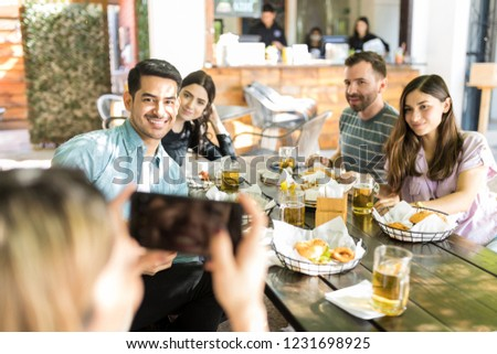 Multiracial friends posing while woman clicking their picture at table #1231698925
