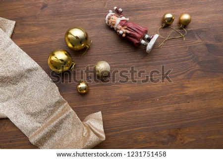 Christmas composition. Christmas gift, gold ribbon, gold balls on Christmas tree, toy souvenir girl on dark wooden background. Flat position, top view, copy space. #1231751458