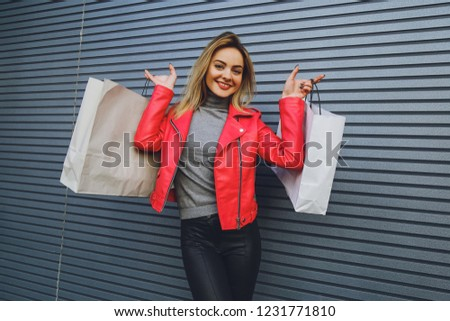 Young beautiful blonde girl with purchases, packages after shopping #1231771810