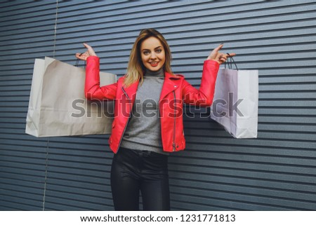 Young beautiful blonde girl with purchases, packages after shopping #1231771813