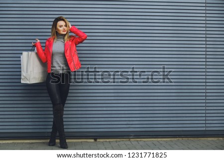 Young beautiful blonde girl with purchases, packages after shopping #1231771825