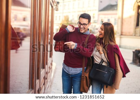 Beautiful young couple enjoying in shopping, having fun together. Man pointing at store window. #1231851652