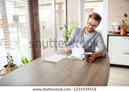 Cheerful male landlord sitting by desk in the kitchen and looking at lease contract at well lit and spacy kitchen room. #1231934458