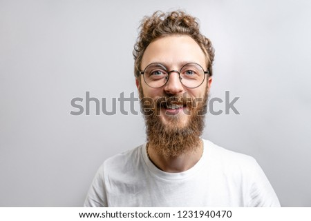 Portrait of young handsome hipster man with beard smiling laughing looking at camera over white background. #1231940470
