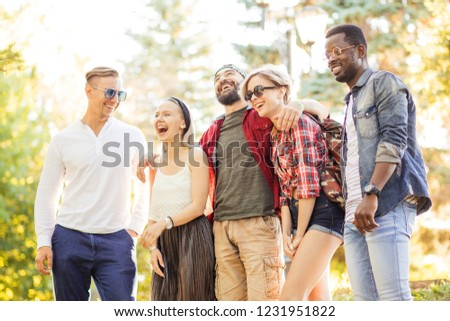 Stylish young people adult men and women using smartphone visit public park during their day off, making a group photo in park. Guys wearing casual clothing and sunglasses. #1231951822
