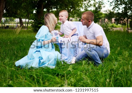 "Happy family together in summer garden/park. Mother and father holding inscription ""family"" . Mother kising. son. Outdoor photo #1231997515"