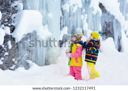 Children play with icicle in snow. Kids lick icicles at frozen mountain waterfall on family Christmas vacation in winter. Outdoor fun in snowy park by cold weather. Kid playing with ice in forest. Royalty-Free Stock Photo #1232117491