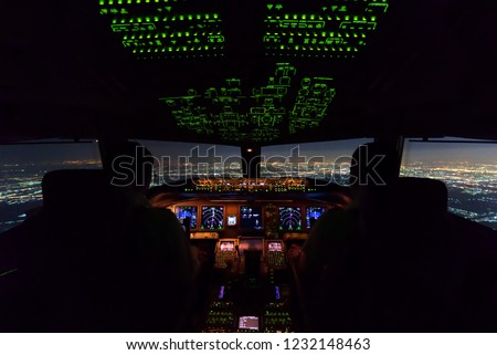 Two pilots are flying the airplane in final approach phase to the runway in night time. Cityscape and airport are seen outside cockpit. Pilots and airplane instruments are inside cockpit. #1232148463