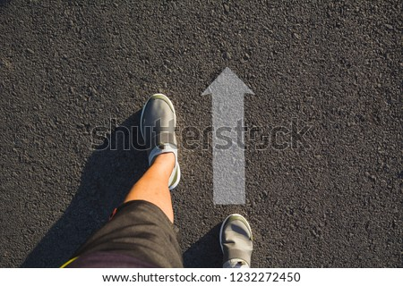 Top view of man wearing shoes choosing a way marked with arrows. Chooses the right path concept. #1232272450