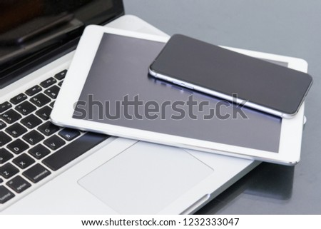 pile of laptop computer and digital tablet electronic devices with blank black screen on table in office #1232333047