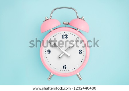 Alarm clock. Fork and knife instead of clock hands. Concept of intermittent fasting, lunchtime, diet and weight loss #1232440480
