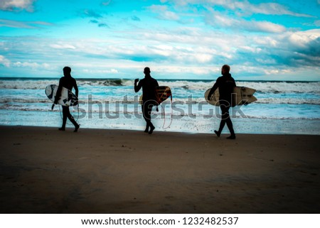 Ogunquit, Maine, USA: November 7th, 2018:  Three surfers silhouetted against a cloudy blue sky walking along the tide line looking at stormy ocean swells. #1232482537