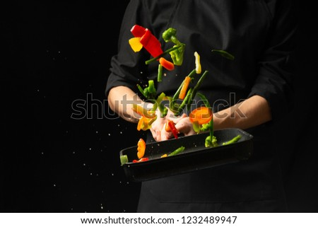Professional cook. He prepares a dish with vegetables in a saucepan. on black background, menu, recipe book, healthy food #1232489947