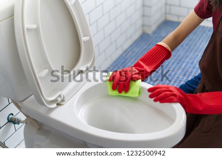 Asian girl with red rubber gloves is cleaning toilet bowl by using toilet wipe. She is sitting and cleaning the bathroom. Seen in top side view. Happy toilet cleaning concept. #1232500942