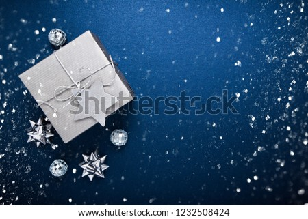 Merry Christmas and Happy Holidays greeting card, frame, banner. New Year. Noel. Silver Christmas gifts, ornaments on blue background top view. Winter holiday xmas theme. Flat lay. #1232508424