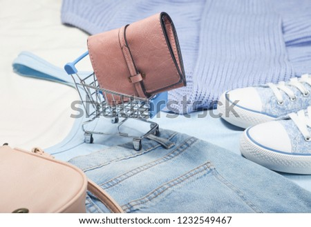Leather wallet in a mini shopping trolley on the background of things and accessories. Concept of shopping, consumer