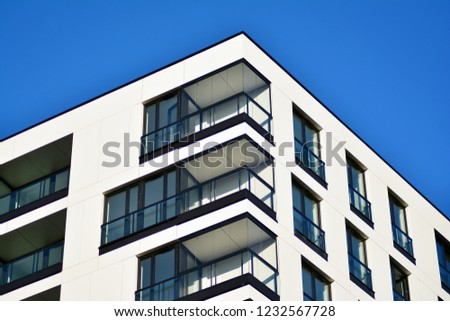 Fragment of a facade of a building with windows and balconies. Modern home with many flats. #1232567728