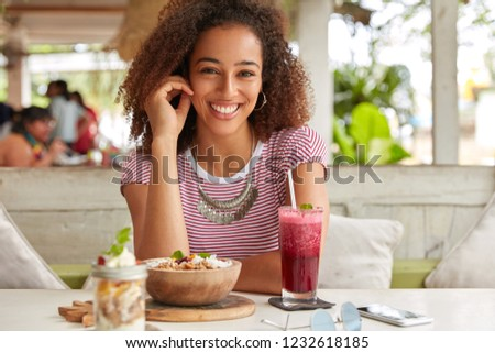Photo of attractive black woman has Afro hairstyle, dressed in casual t shirt, smiles broadly at camera, rejoices meeting with colleague in cozy cafe, drinks fresh smoothie, likes exotic food #1232618185