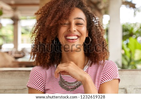 Headshot of glad woman laughs and smiles broadly, expresses positive emotions, has hilarious expression, wears round big earrings and necklace, spends time in cafe. Afro American teenager indoor #1232619328