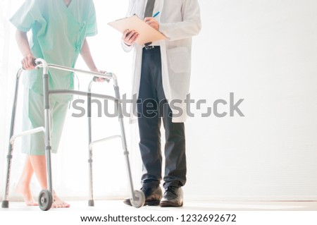 A  male doctor is helping a patient to try walking #1232692672