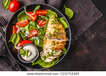Chicken breast salad with spinach, tomatoes and Caesar dressing, dark background, top view. #1232752684