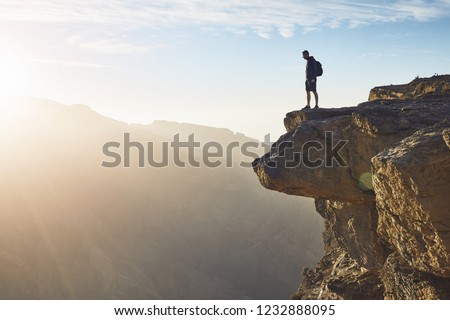 Young tourist with backpack standing on the edge of cliff at sunrise. Jebel Akhdar, Grand Canyon of Oman.   Royalty-Free Stock Photo #1232888095