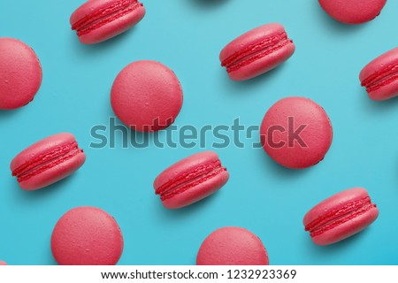 Macaroons on colored background, a pattern of colorful french cookies macarons. Beige, brown french cookies macarons on red background. Gift for Valentine's Day #1232923369
