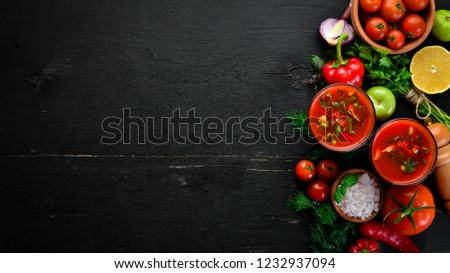 Gazpacho Soup in Glas. Tomato soup with onion, paprika and parsley. Italian cuisine. Top view. On a black background. Free space for text. #1232937094
