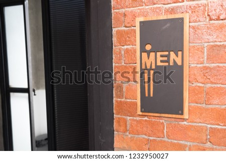 public restroom or toilet with man signs on brick wall decorate