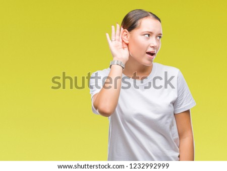 Young beautiful caucasian woman over isolated background smiling with hand over ear listening an hearing to rumor or gossip. Deafness concept. #1232992999