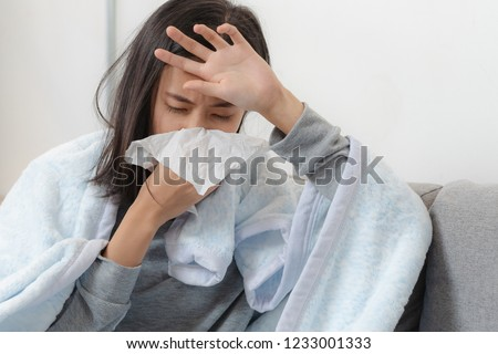 Sick day at home. Asian woman has runny and common cold. Royalty-Free Stock Photo #1233001333