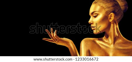 Gold Christmas Woman. Beauty fashion model girl with Golden make up, hair and jewellery, pointing hand on black background. Gold glowing skin. Metallic, glance Fashion art portrait, Hairstyle, make up #1233016672