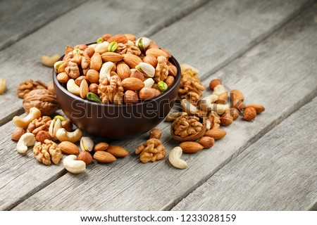 Wooden bowl with mixed nuts on a wooden gray background. Healthy food and snacks, organic vegetarian meals. Walnut, pistachios, almonds, hazelnuts and cashews, walnut. #1233028159