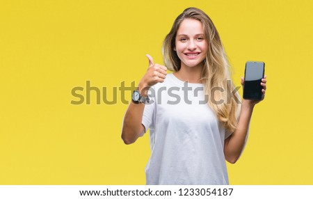 Young beautiful blonde woman showing screen of smartphone over isolated background happy with big smile doing ok sign, thumb up with fingers, excellent sign #1233054187