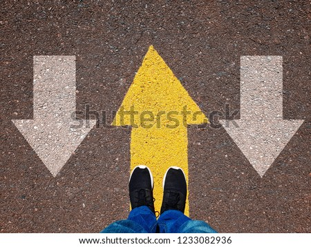 Opposing direction arrows on asphalt ground, personal perspective concept for finding your own way #1233082936