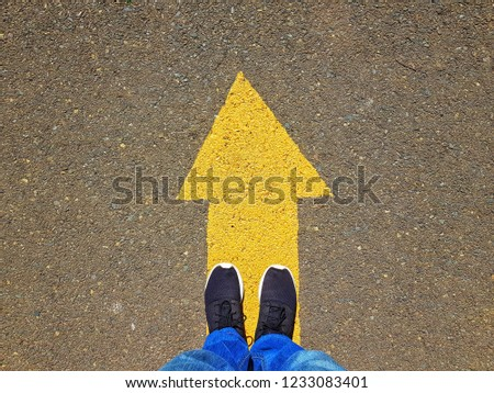 low section of a man standing on yellow arrow on asphalt ground #1233083401